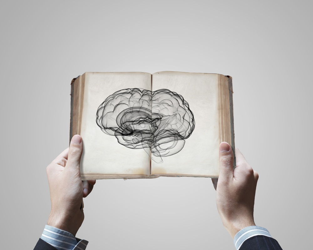 Close up of male hands holding opened book with brain picture.jpeg